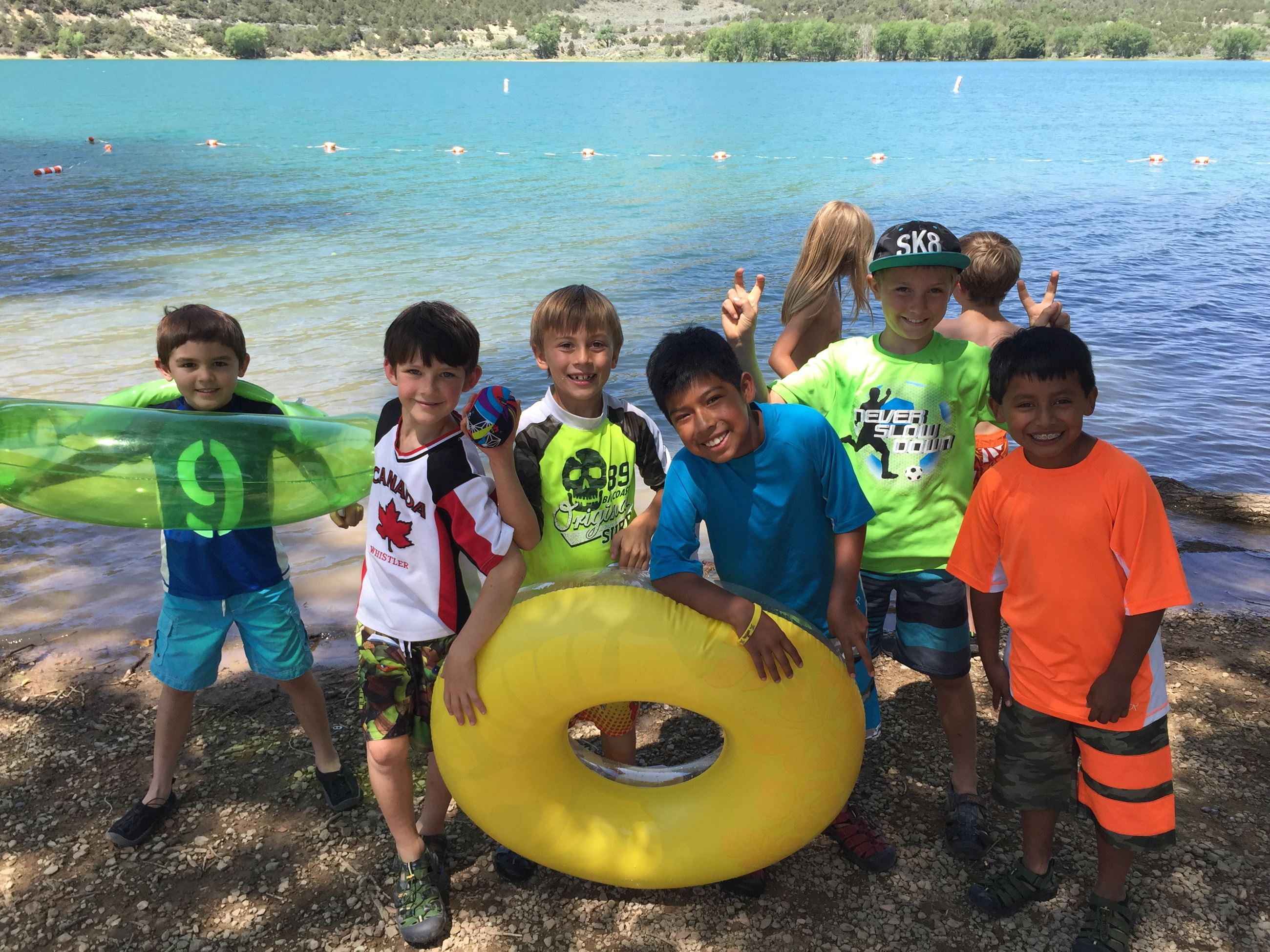 Six boys in front of a lake with inner tubes smiling for the camera
