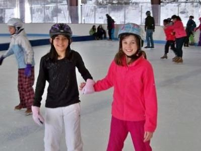 Two girl skaters holding hands skating on the rink