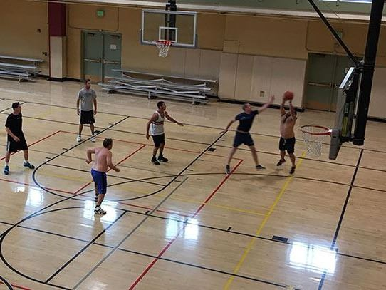 Group of six men playing basketball in gymnasium