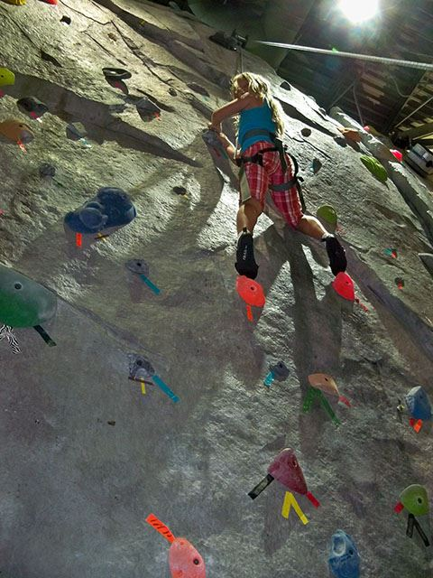 Young girls looking down from halfway up a climbing wall